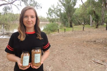 Pic of Erin holding her produce in front of the Murray River