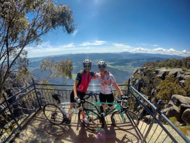 Pic of Michelle and Kerry at an overlook in the mountains with their bikes