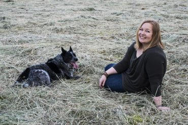 Jasmine Glover sitting relaxing in field with her dog