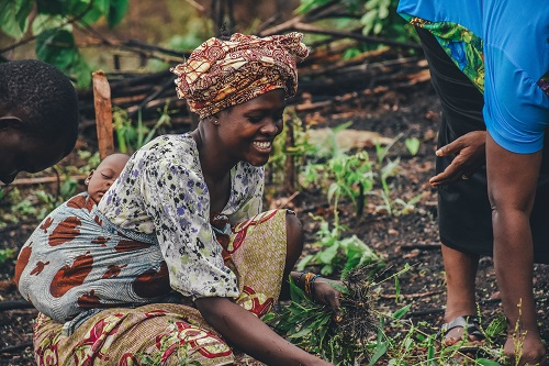 African woman with baby on back working on farm