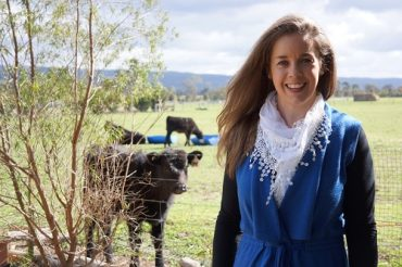Rural entrepreneur Elizabeth Wharton in field next to cow
