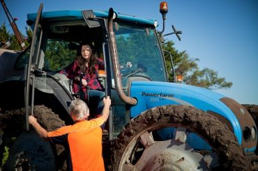 Woman in tractor talking to man