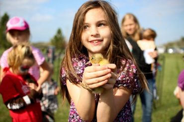 Smiling girl holding duckling