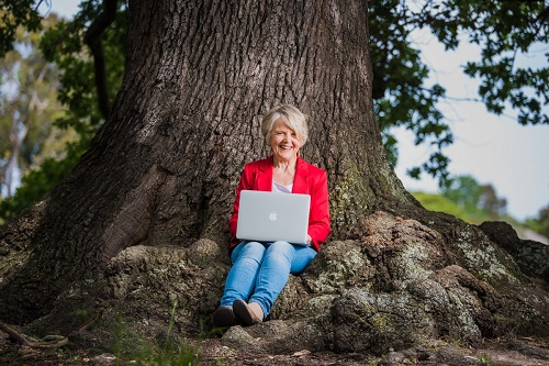 Journalist Dr June Alexander sitting under tree with laptop on knee