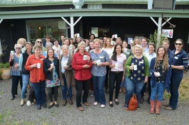 Women's Network gather in front of a country cafe, raising their Country Cuppas-branded mugs