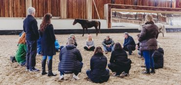 Jess Liston conducting a leadership course where horses teach leadership. Group of people in indoor arena opposite horse