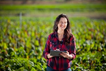 Woman in red checked top standing in field with iPad