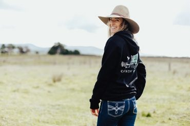 Entrepreneur Megan Lawrence stands in a field wearing one of her navy hoodies from her online clothing business