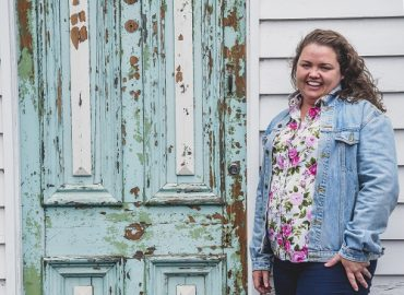 Fifth-generation farmer Jackie Elliott stands in front of rustic blue farmhouse door