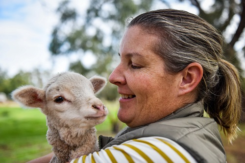 Farmer Carly Noble holds a newborn lamb in the paddock