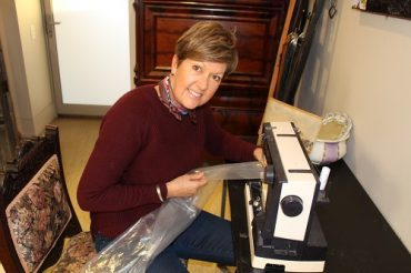 Jill Whiting sits at her sewing machine