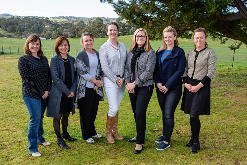 Claire Moore, 2019 AgriFutures Victorian Rural Women's Award winner stands in a field with six other state award finalists