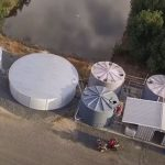 Aerial photo of chicken farm water tanks and shed next to a dam.