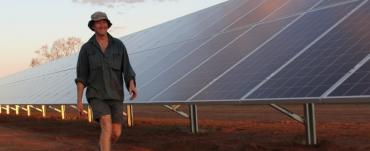 Man walking next to solar panels
