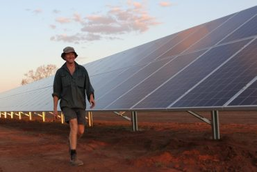 Image shows a man walking past an array of solar panels