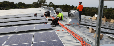 3 men fitting solar panels to a roof