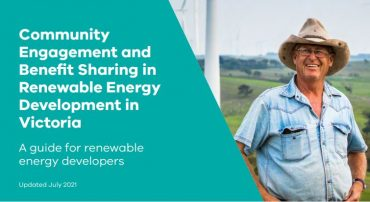 Image of farmer smiling in front of a wind turbine