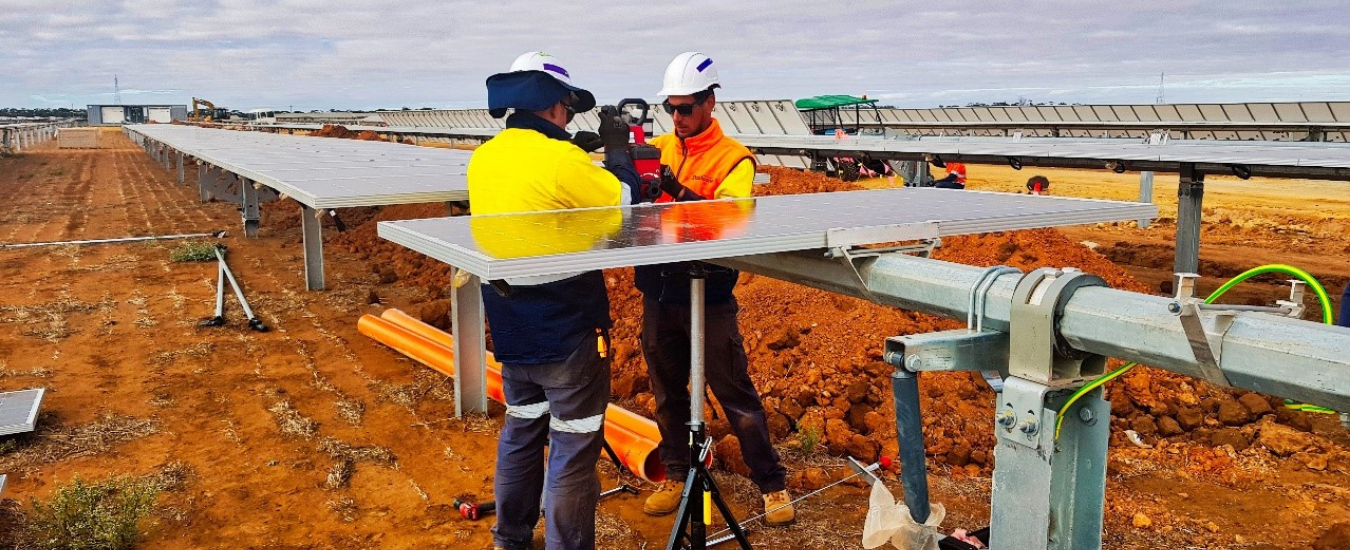 Two men dressed in Hi Vis working on a solar panel