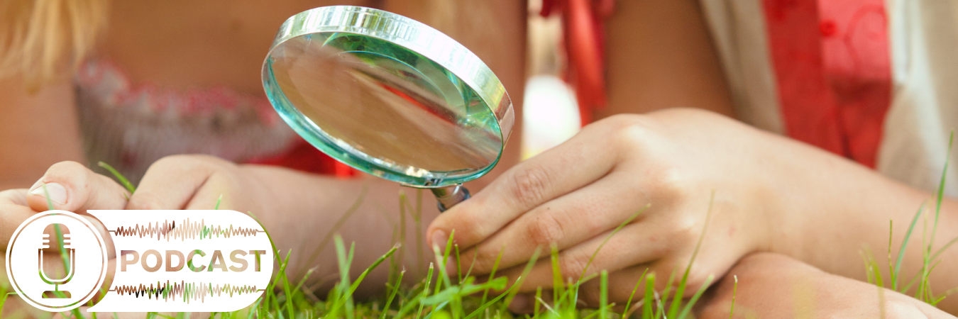 Children with magnifying glass in the grass