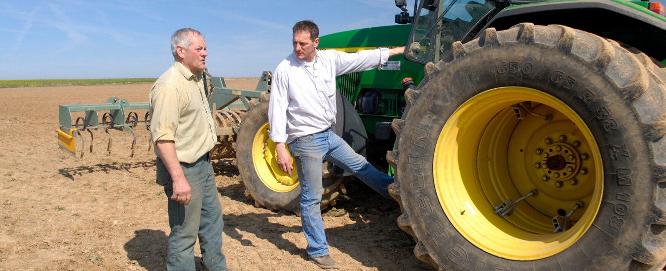 Two farmers talking at a tractor in a paddock