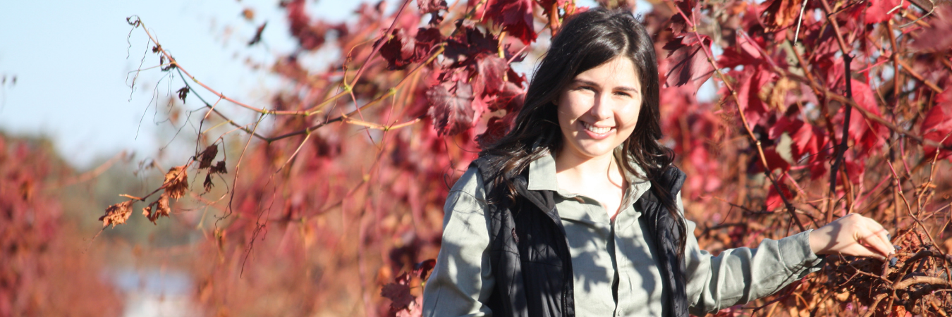 Woman standing next to autumn vines