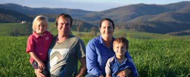 Jen and Brad Smith stand in a crop paddock on their farm. Jen is holding their son and Brad is holding their daughter.